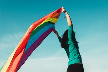 unrecognizable_young_girl_raising_gay_pride_flag_above_her_head.jpg